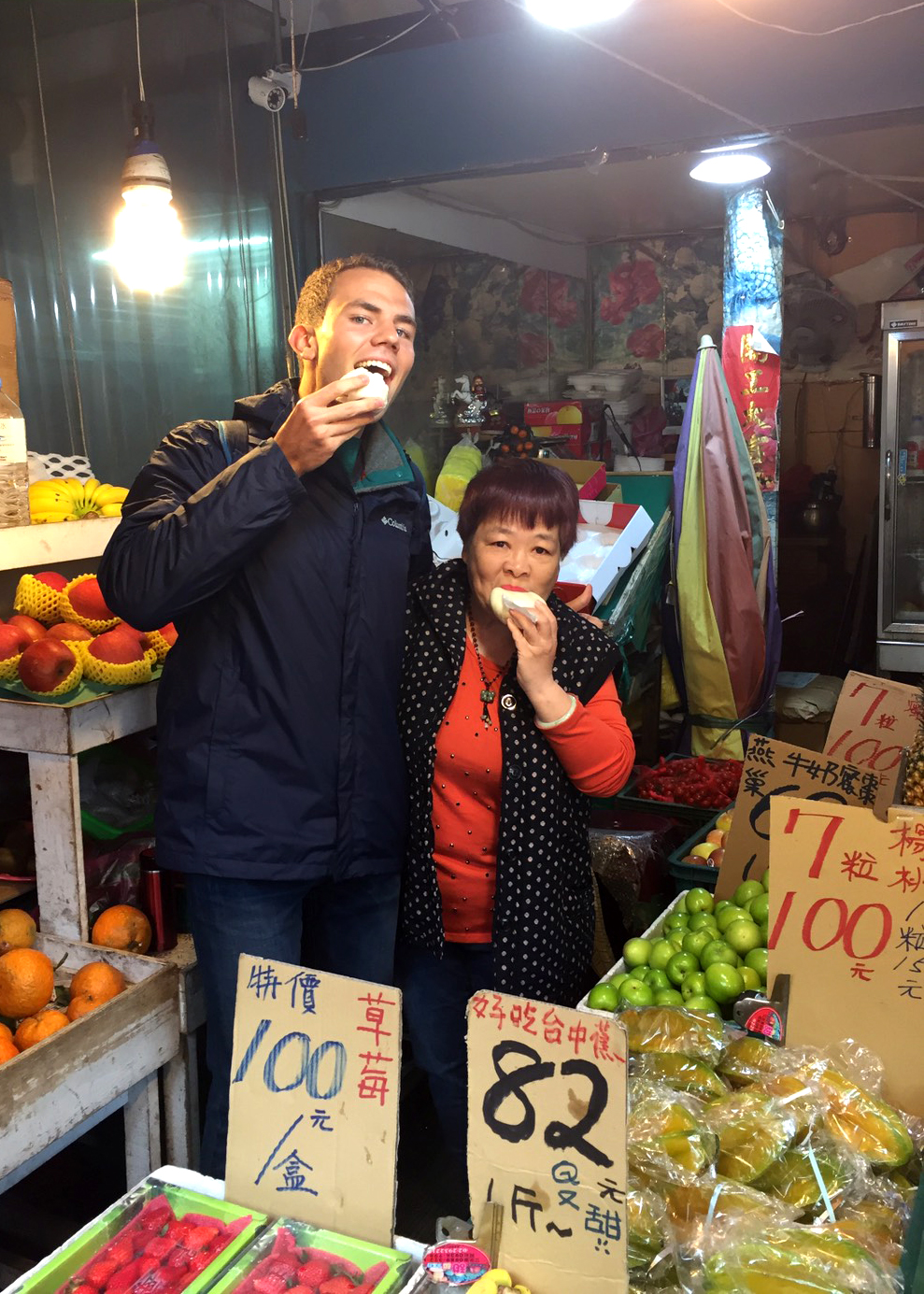 Young man standing next to older woman holding food in their mouths in the middle of a stand with fruits for sale