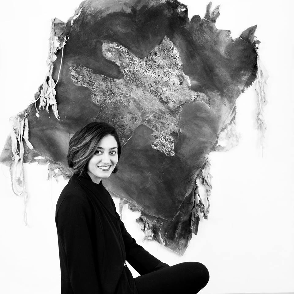 Woman smiling in front of a hanging textile art piece