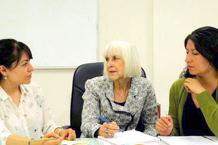 Three women sitting and talking in a classroom