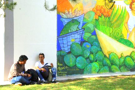 Two men sit outside against building with colorful art on it
