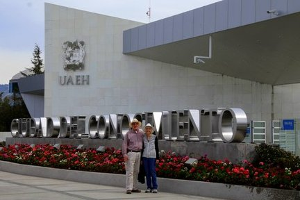 Man and woman stand in front of a building sign
