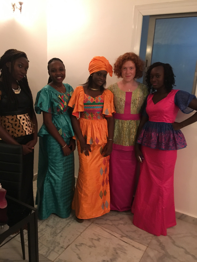 Group of five women pose in colorful Senegalese dresses.