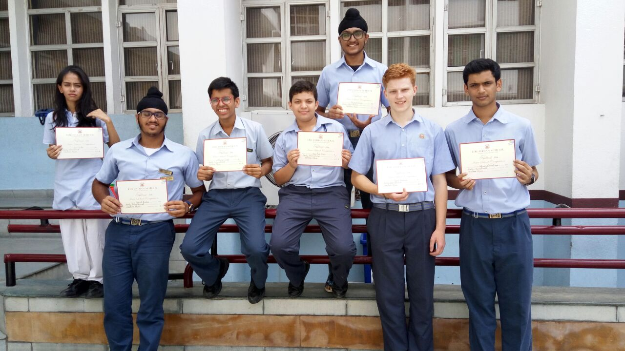 Group of young adults holding up certificates