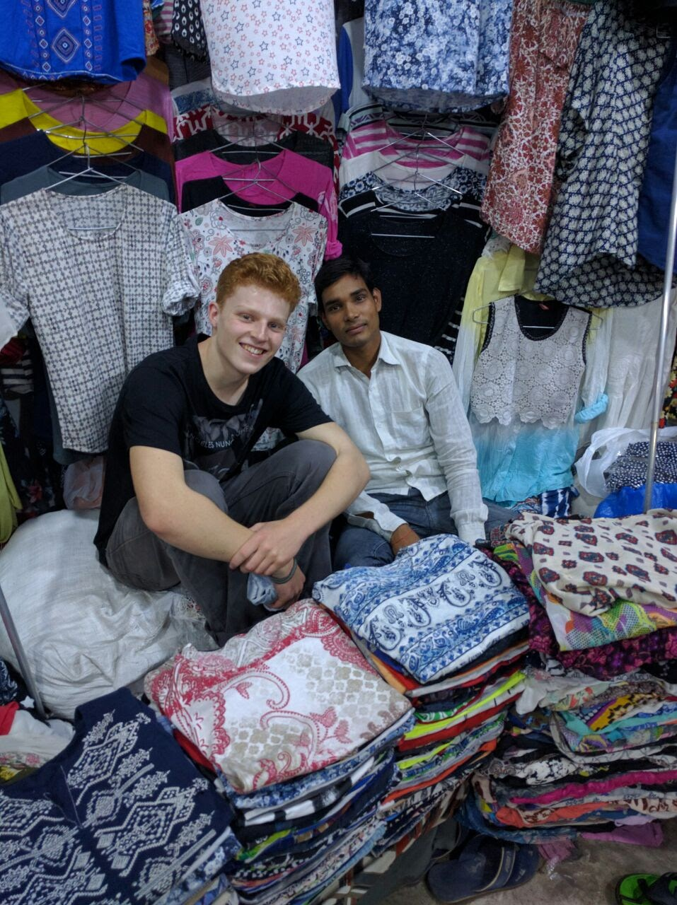 Young guy sits next to a man in the middle of fabric piles and clothes hanging in a store