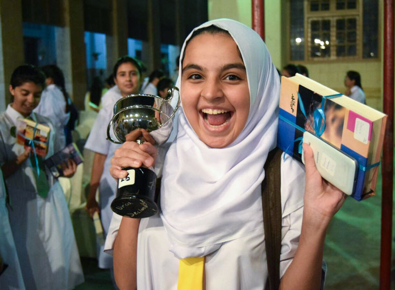 Young woman wearing hijab smiles hard holding up a book and a trophy