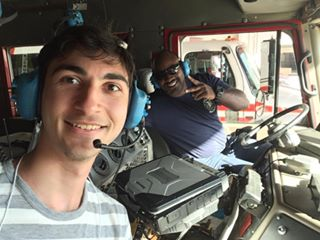 Two men in  the front seat of a truck, one wearing large work headphones