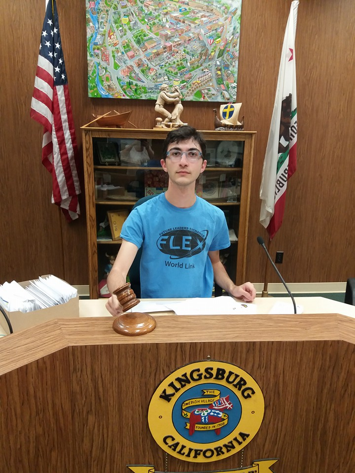 Young male sits at desk holding gavel with city symbol on front of desk