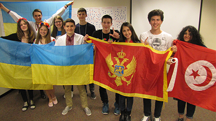 Dina (third from right) poses with the flag of Montenegro during an activity at her host school.