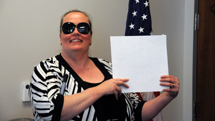 Dr. Gilson at her FFSB swearing-in ceremony.  She is holding a certificate printed in Braille.