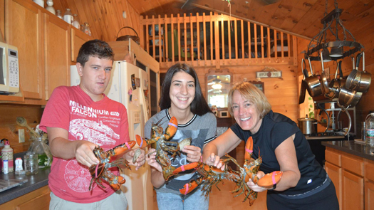 Three people holding lobsters and smiling