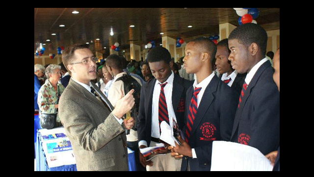 Scott Johnson of North Hennepin Community College and other recruiters advise students at a College and Career Fair in Abuja, Nigeria
