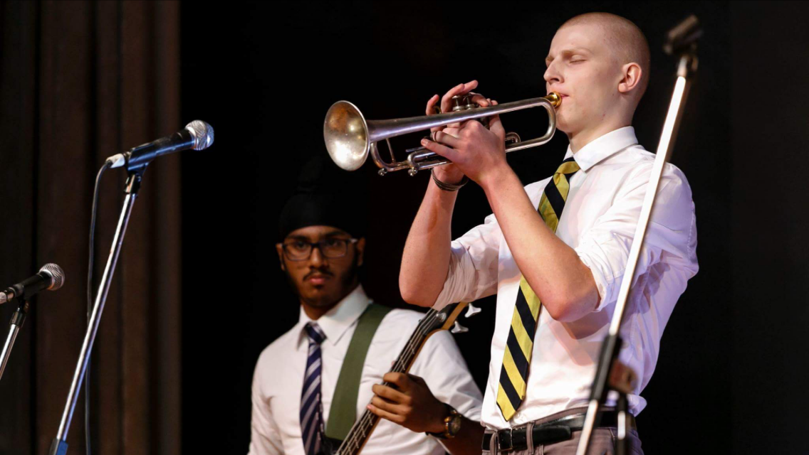 Young man plays trumpet on a stage in front of a mic with another young man in the background on a guitar