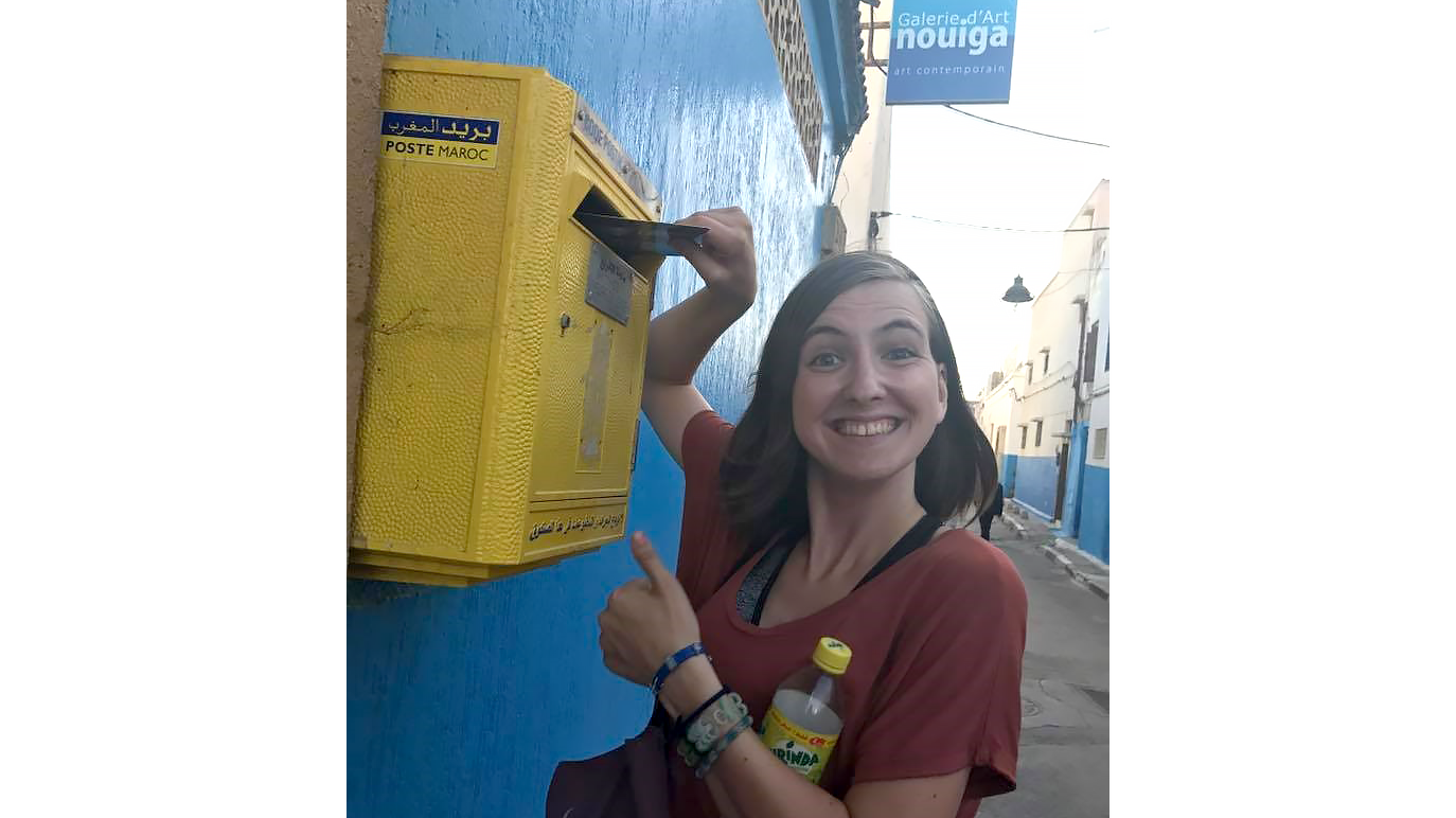 Woman placing mail in a mailbox while looking at the camera smiling with a thumb up