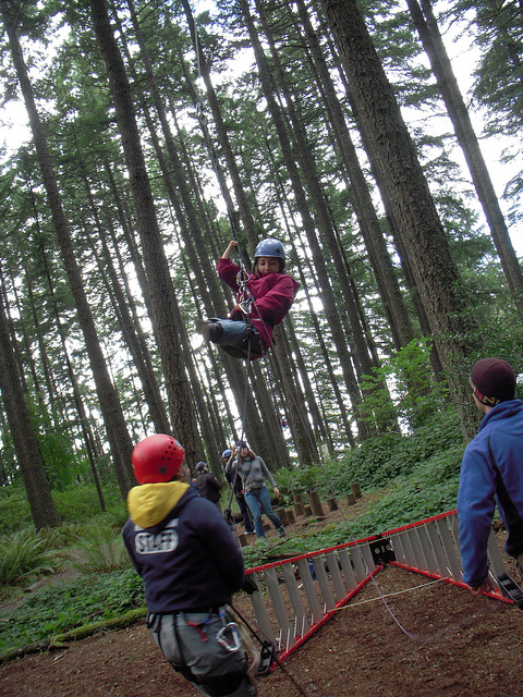 Azima on a ropes course with Mobility International USA in Eugene, OR