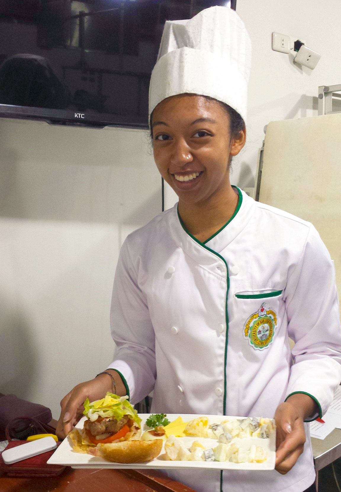 Young woman in chef attire holding plate of food
