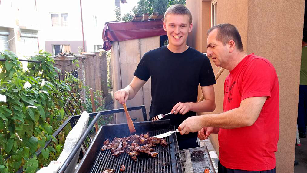 Teenage boy smiling and helping flip meat on a grill with an older man