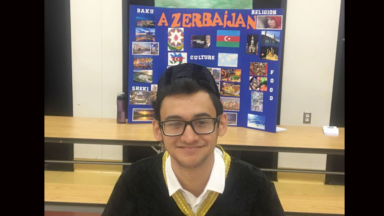 Young man wearing glasses and baseball hat to the back, sits smiling in front of display on Azerbaijan