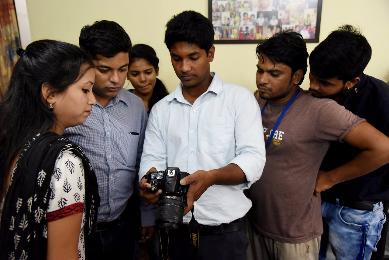 Young man holding a fancy camera surrounded by a group of young adults observing his actions with the camera