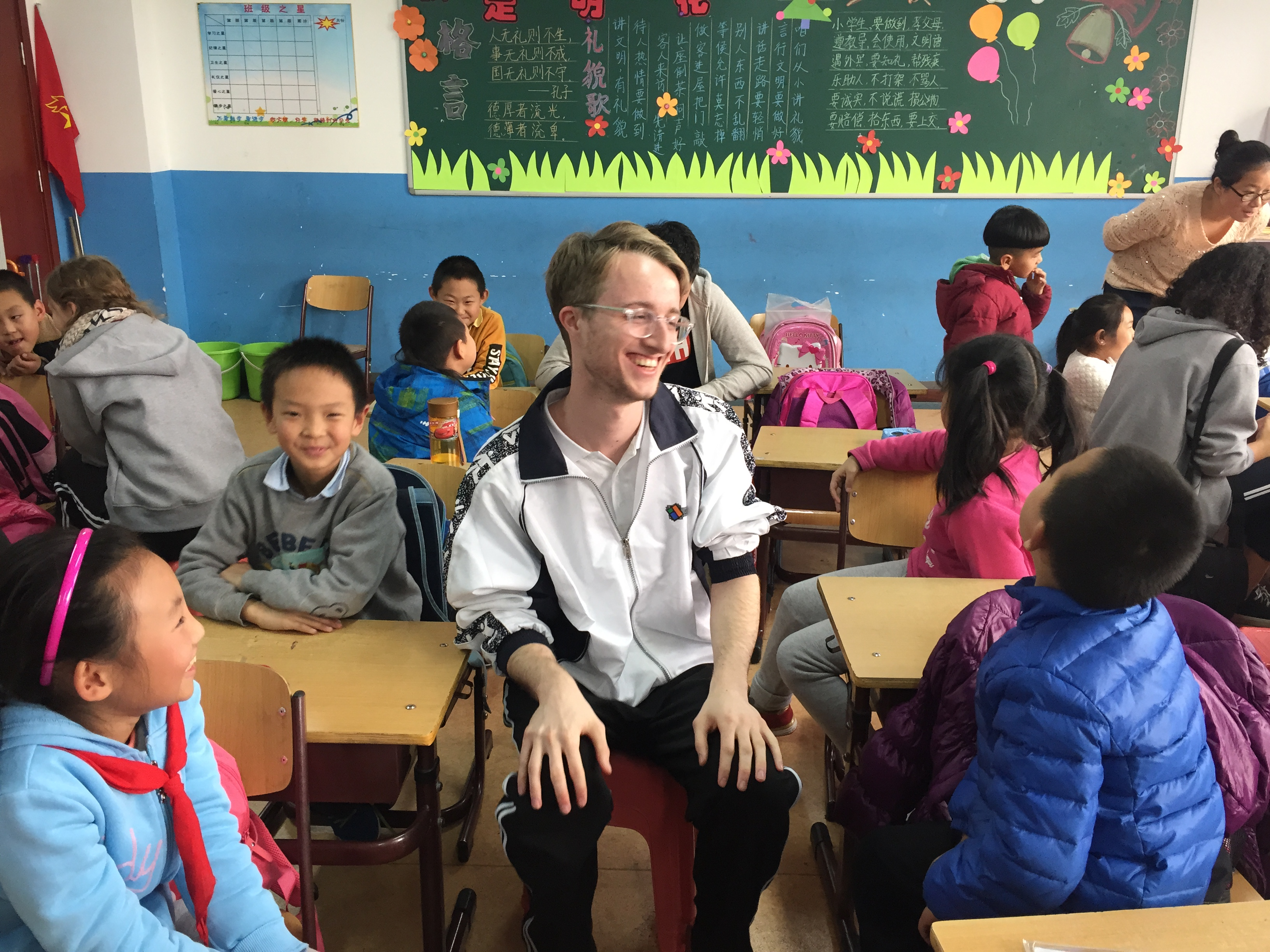 Ryan sits in the middle of young chinese children in a classroom