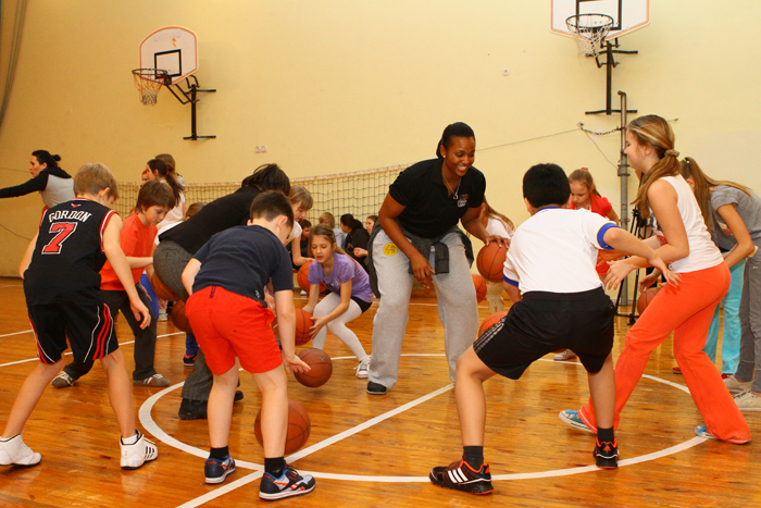 Young Ukrainian athletes learn new dribbling techniques during a fun basketball activity with Tamika Raymond.