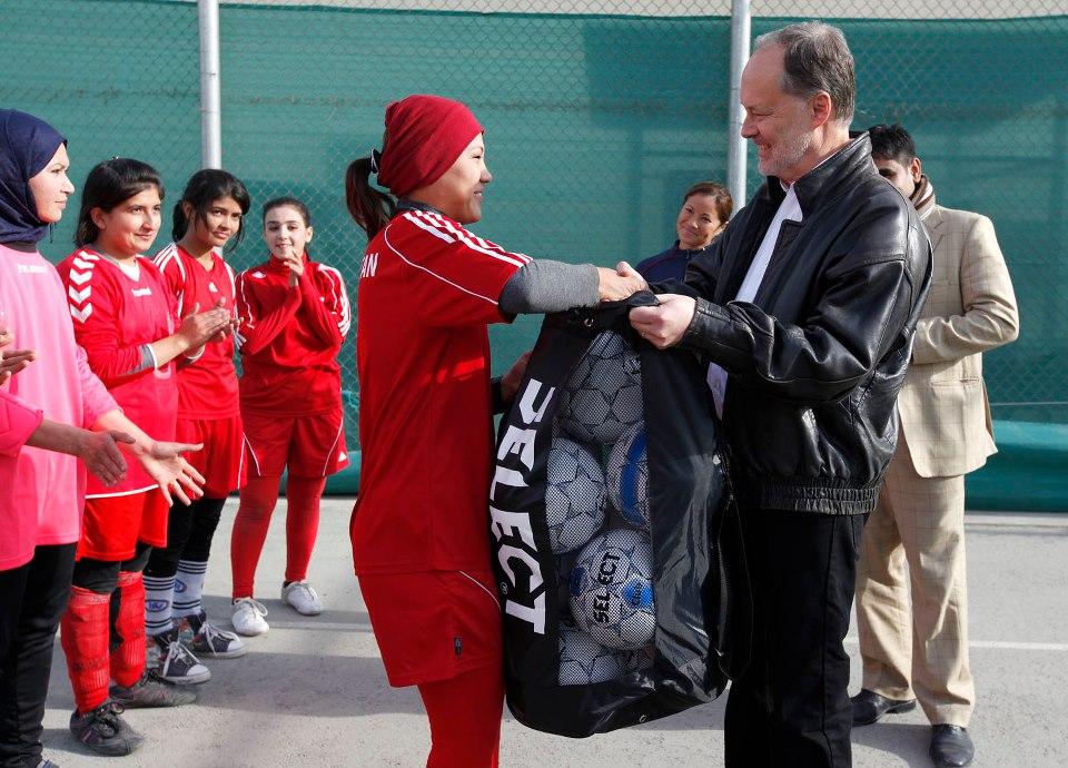 Ambassador James Cunningham with a member of the Afghan Women's National Soccer Team.
