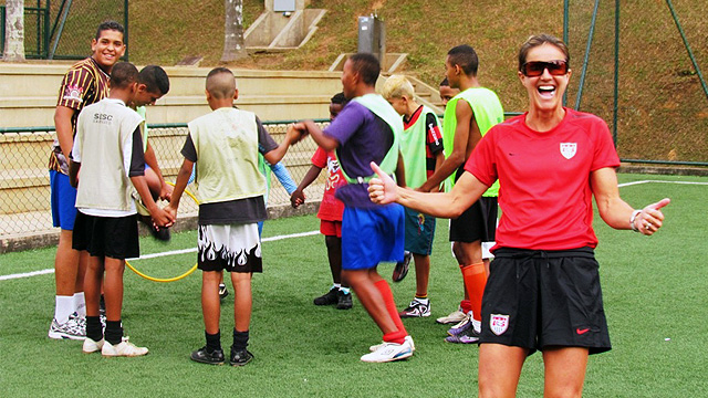 Brandi Chastain shows her enthusiasm for the teenage boys team as they engage in team building activities.