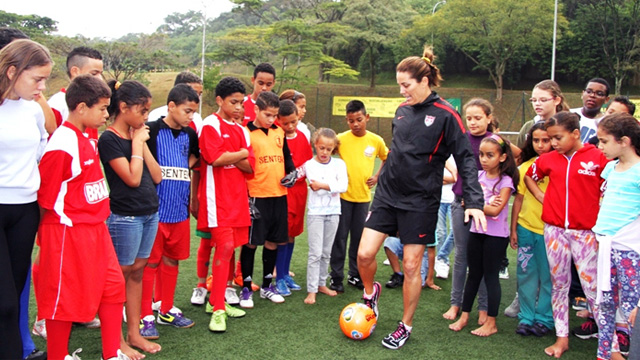 Julie Foudy shares her expert tips on kicking techniques with young female clinic participants in a neighborhood outside of São Paulo.