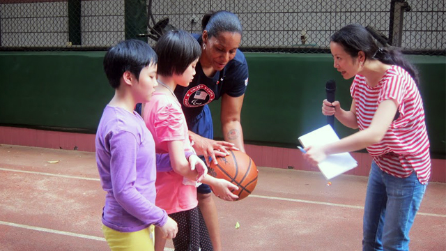 Dr. Woodson-Smith assists a blind student with a basketball at Peiying Vocational School.