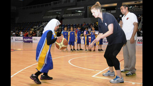 NBA representative Becky Bonner works with a young Indonesian girl on the court.