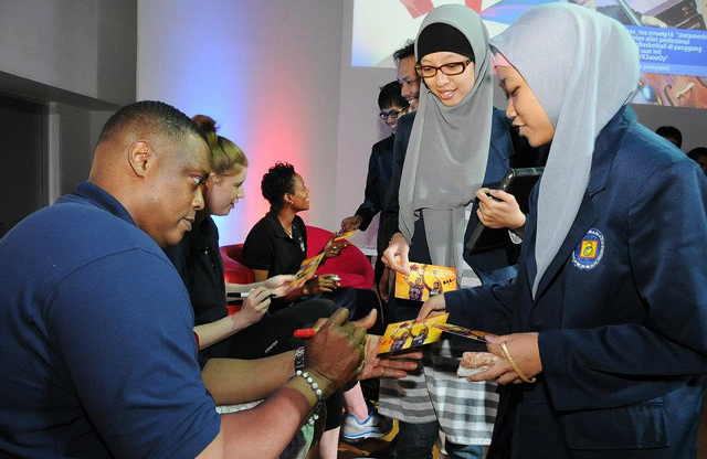 Rick Mahorn, Becky Bonner, and Edna Campbell sign autographs for the participants in Indonesia.