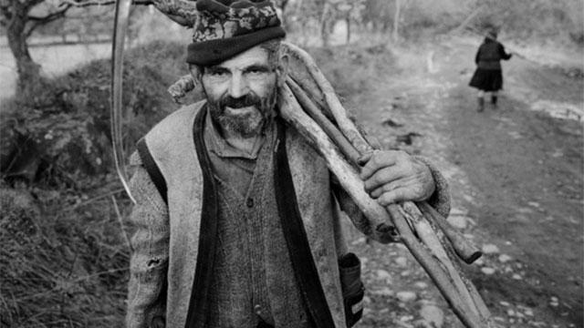 Photo of a man holding sticks and a scythe.