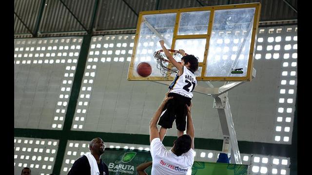 A young Venezuelan boy slam dunks with the help of Greivis Vasquez.
