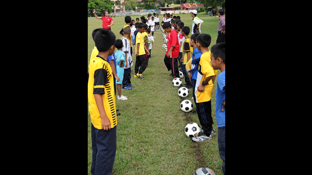 Danielle Slaton lines up with the young Malaysians at a soccer clinic.