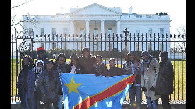 The group proudly poses with their national flag in front of the White House during their tour of the nation's capital.