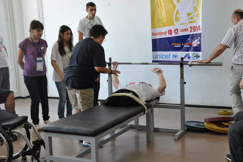 An American participant assists an athlete with their bench press.