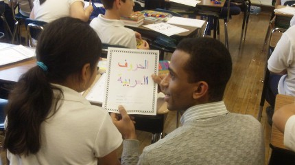 Yasser Abdelgalil is checking students comprehension of Arabic letters as they color in an Arabic alphabet worksheet in October of 2012 at Peck Elementary School in Chicago.