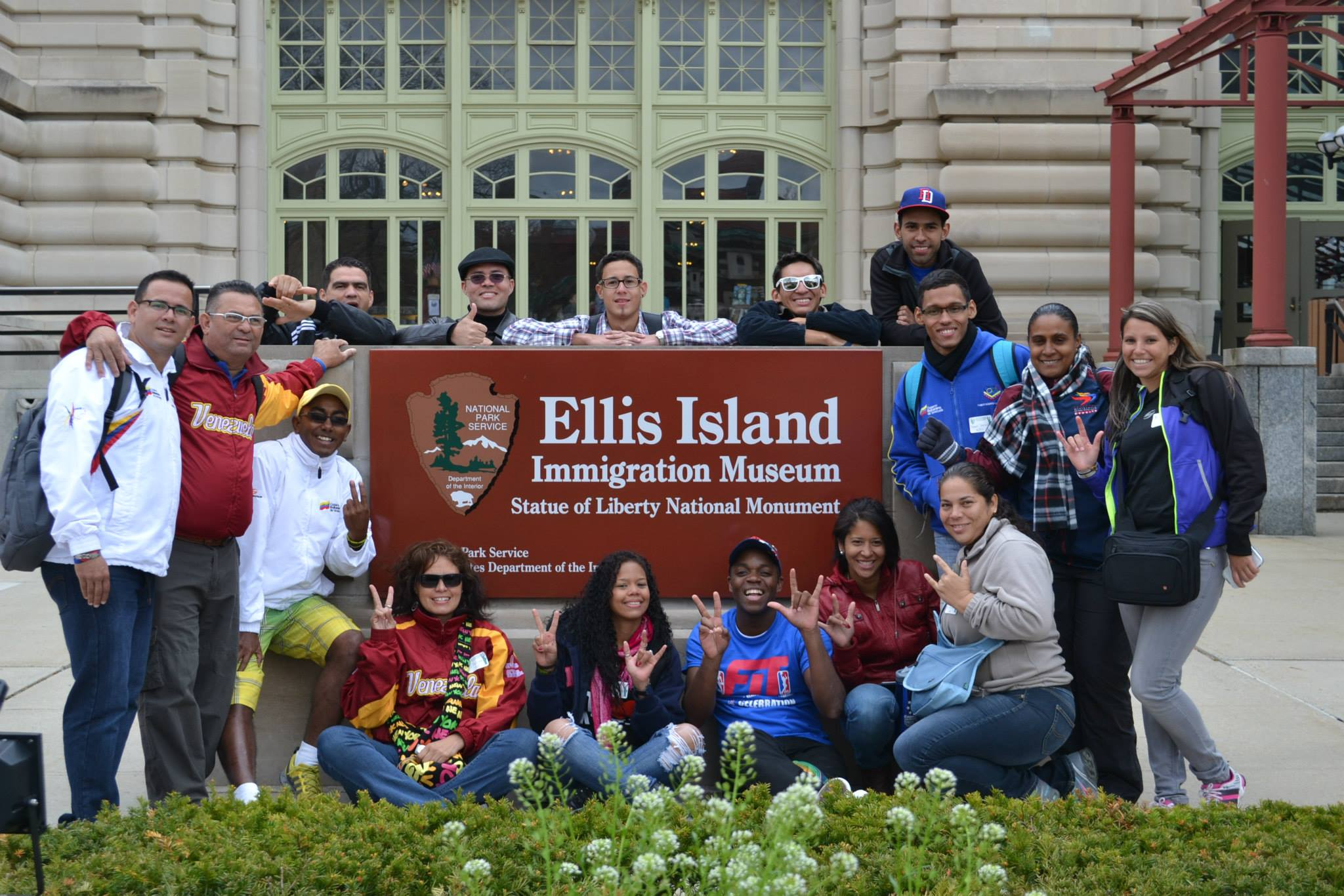 The sports visitors pose around the sign at Ellis Island, NY