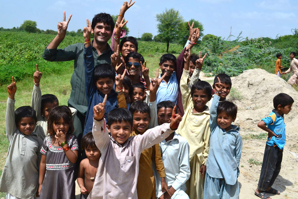 Young man stands with group of small kids all smiling and holding up two fingers
