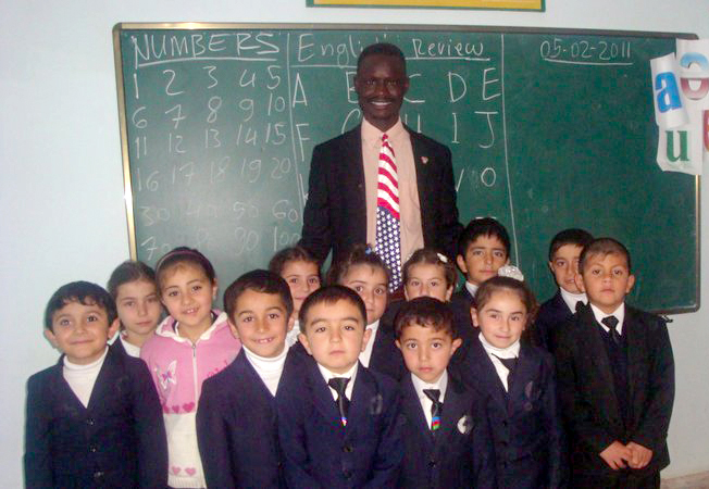 Man stands with group of small children in front of chalkboard