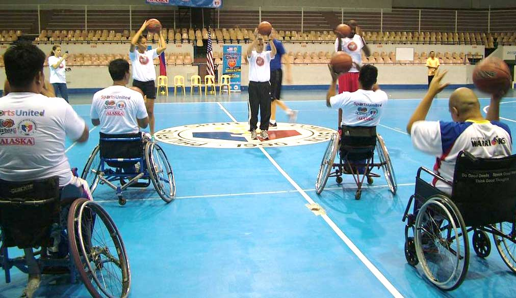 Wheelchair bound participants on the court holding basketballs while learning from the former NBA players