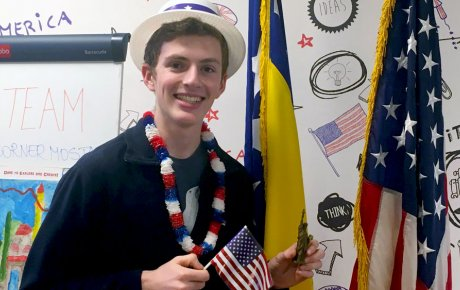 Young man in patirotic hat and lanai holding U.S. flag and miniature Statue-of-Liberty