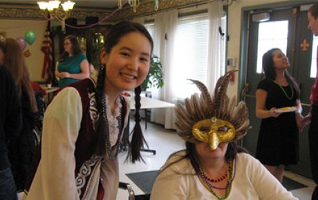 Zhyldyz having fun with a resident at her host community's senior care facility Mardi Gras party that she helped organize