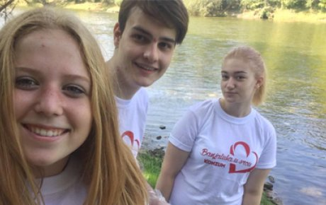 Close up of blonde girl on the left with two teens behind her in front of a river