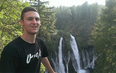 Dusan standing in front of a waterfall.