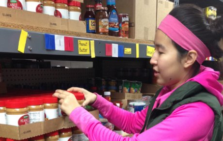 High school age girl stocking peanut butter at food pantry