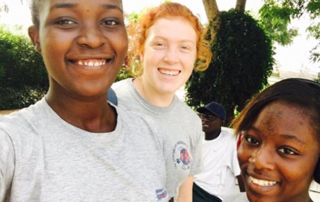 A red-headed girl smiling in a selfie in between two of her Senegalese girl friends.