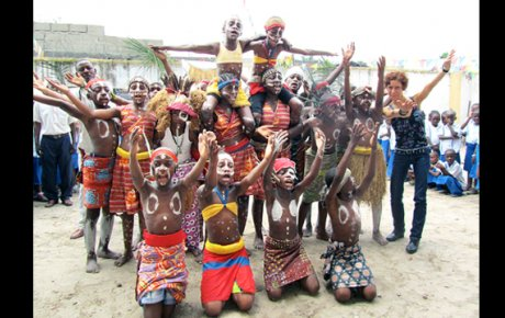 Carmen Smith poses with school children in the Democratic Republic of Congo who performed for her visit.