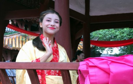 Girl in kimono outfit smiling and waiving
