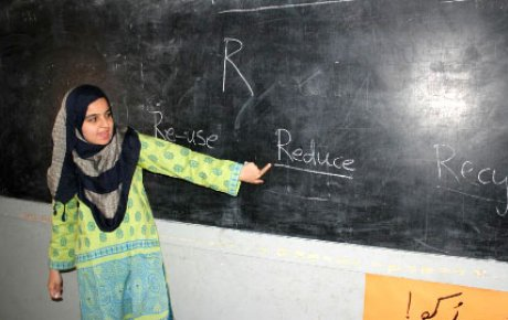 Young woman wear hijab pointing at a chalkboard with the letter R and the words Re-use, Reduce, and Recycle