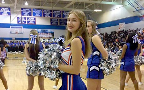 Teen girl in cheerleading outfit stands on court facing camera surrounding other cheerleaders